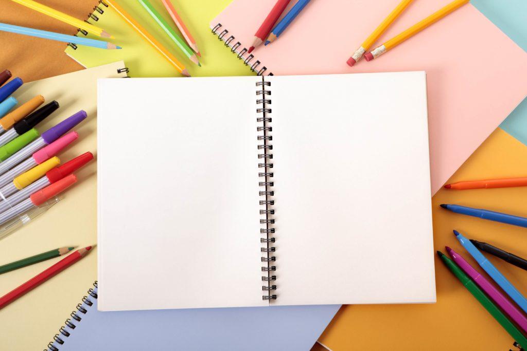 Schreibtisch mit einem Heft und Stiften