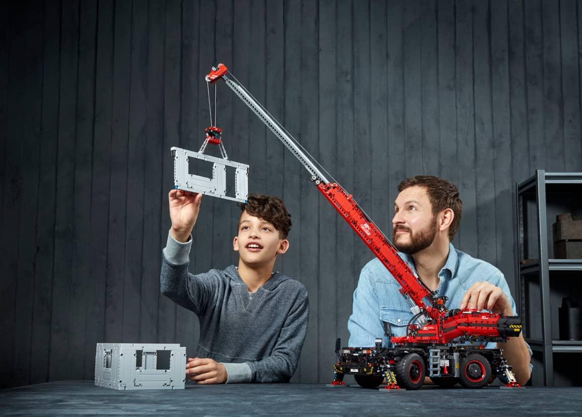 Mann und Kind spielen mit dem geländegängigen Kranwagen 42082