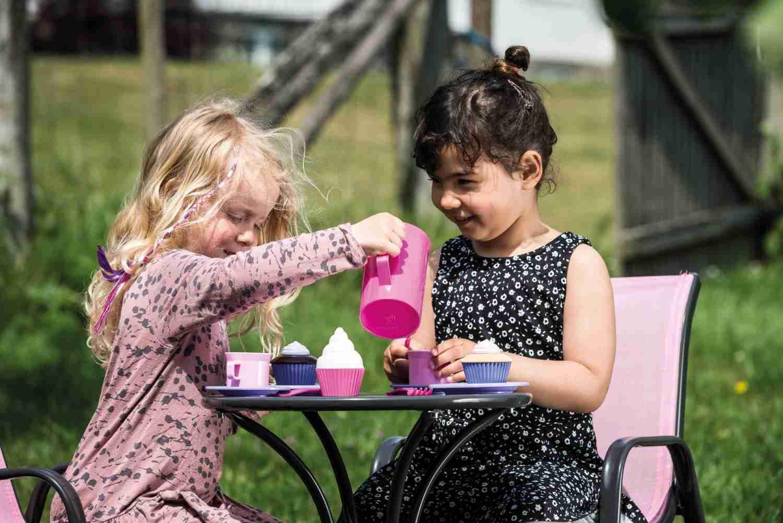 Zwei Mädchen sitzen im Garten und trinken spielerisch Tee