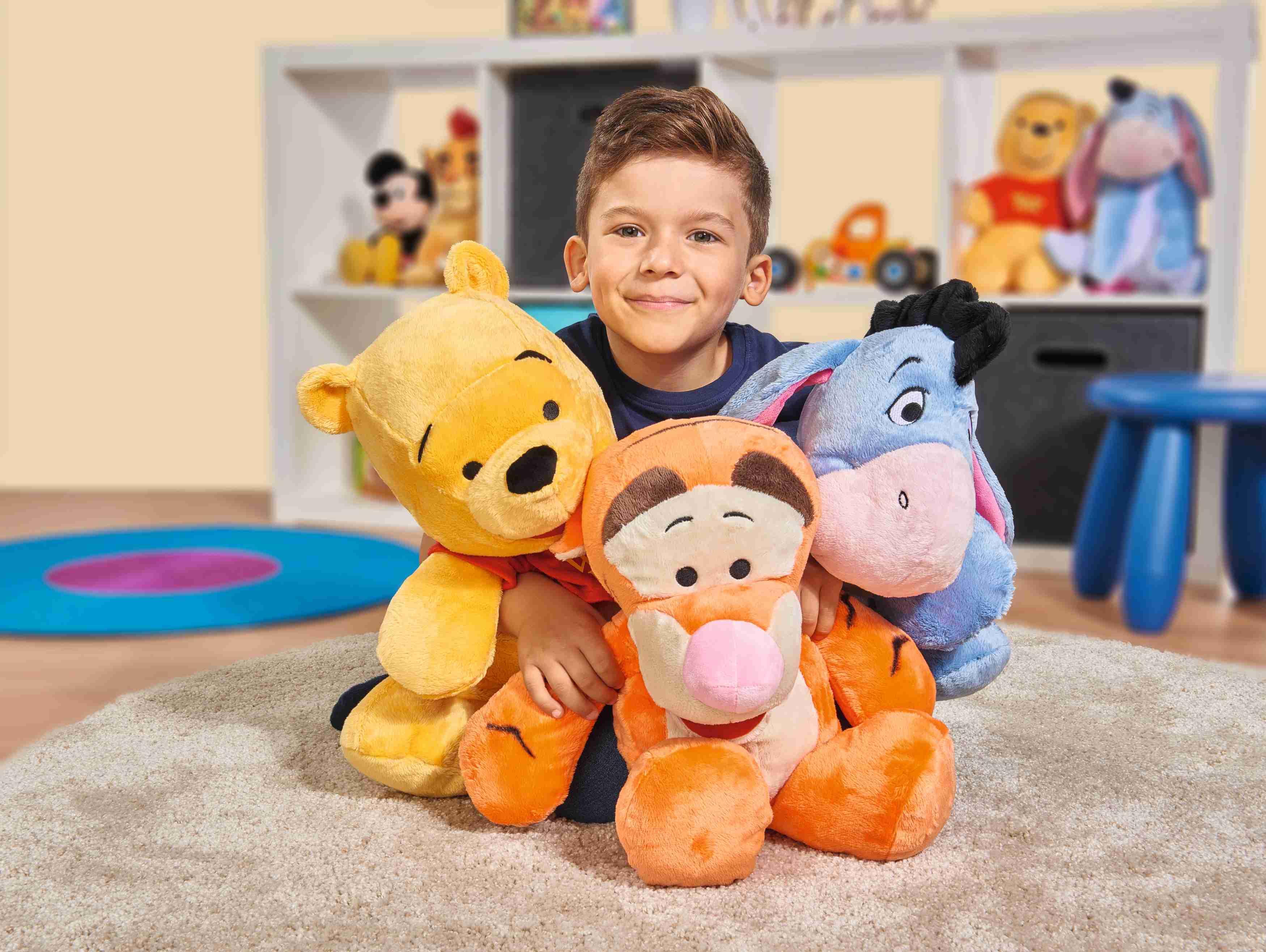 Kind mit Winnie Pooh Kuscheltieren von Simba