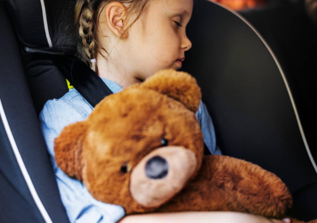 Mädchen schläft im Kindersitz